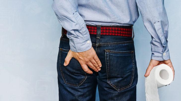 Un homme souffre des hémorroïdes et se tient les fesses